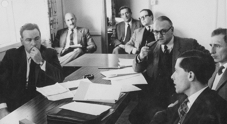 Black and white image of a group of men in some kind of meeting.